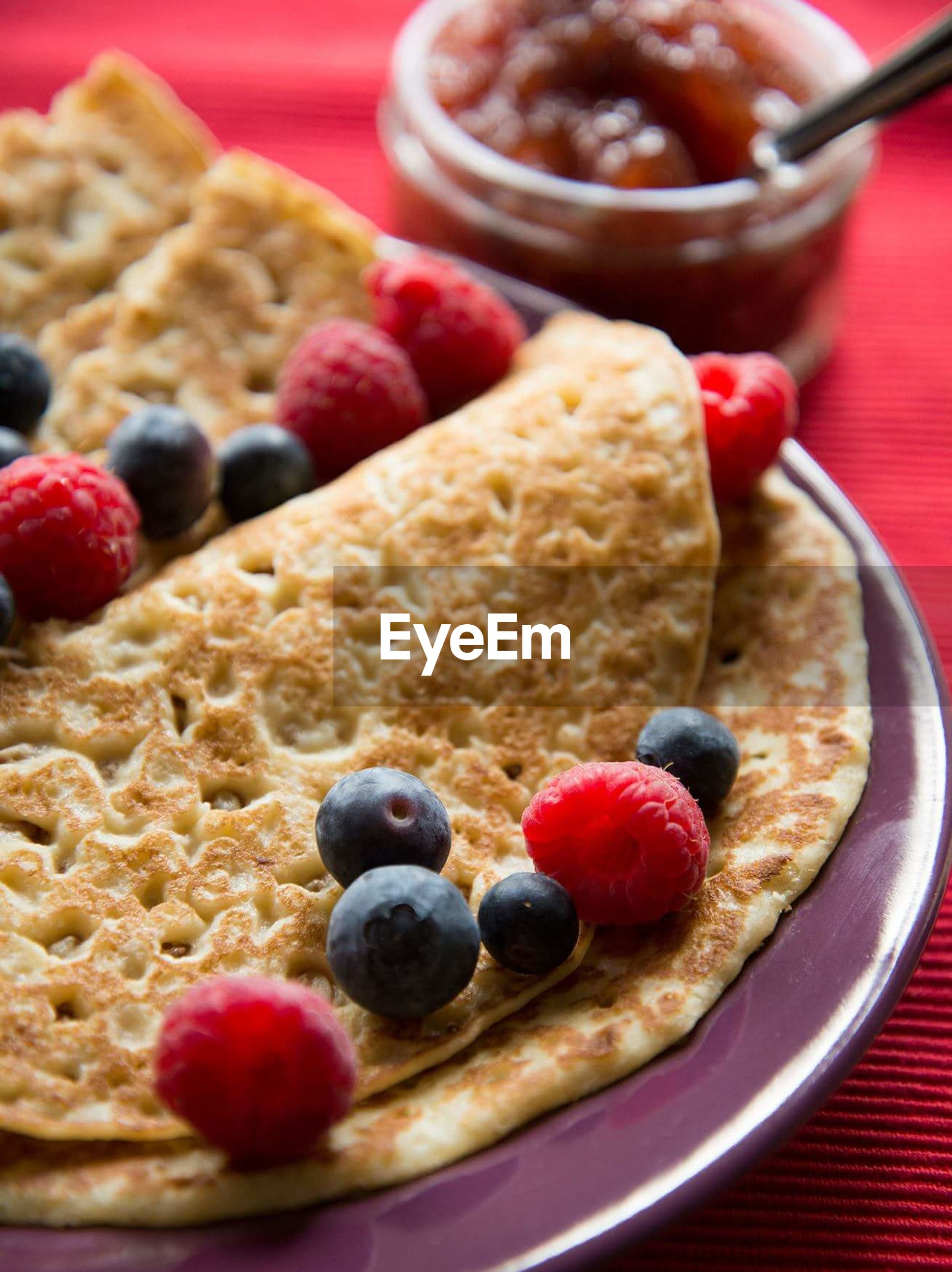 Close-up of crepes with blueberries and raspberries on table