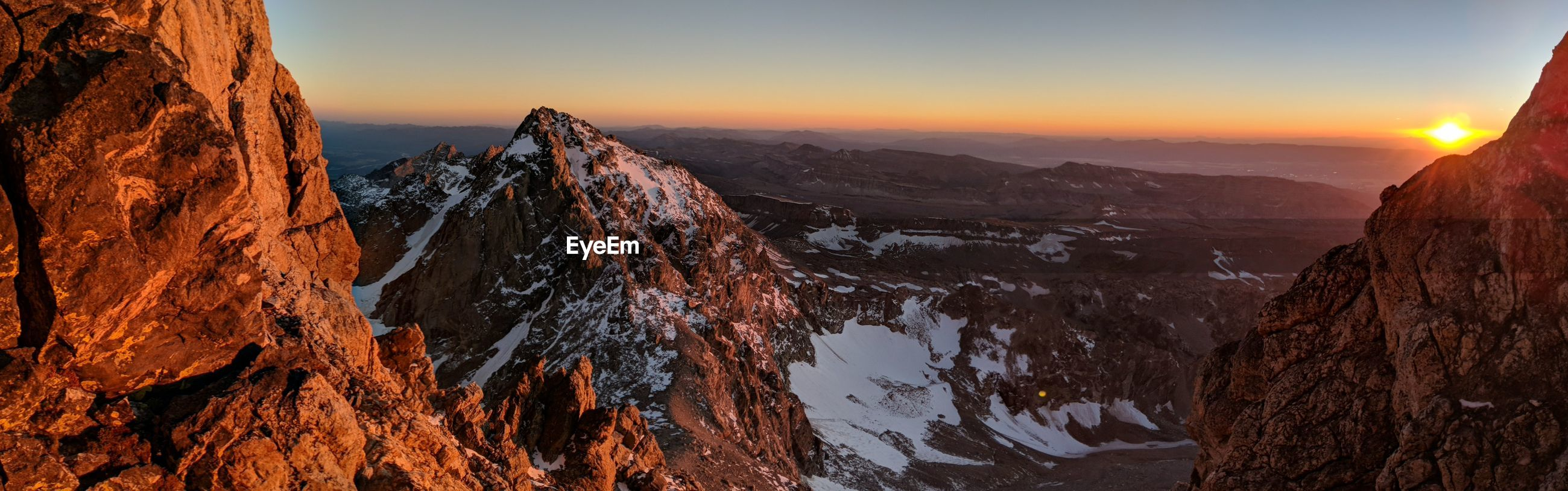 PANORAMIC VIEW OF SNOWCAPPED MOUNTAINS DURING SUNSET