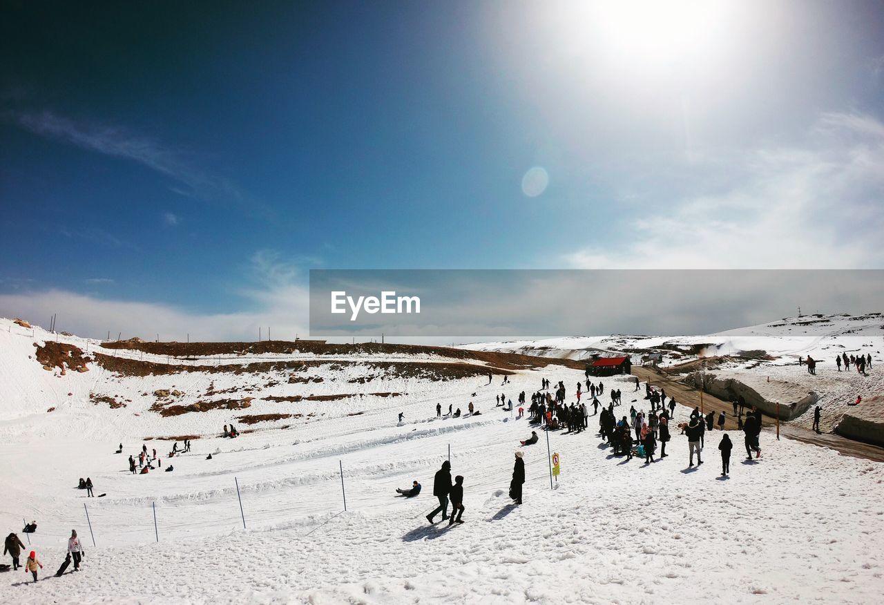sky, winter, crowd, large group of people, snow, cold temperature, group of people, real people, sport, leisure activity, mountain, vacations, scenics - nature, trip, holiday, sunlight, beauty in nature, nature, winter sport, mountain range, outdoors, sun, snowcapped mountain, lens flare
