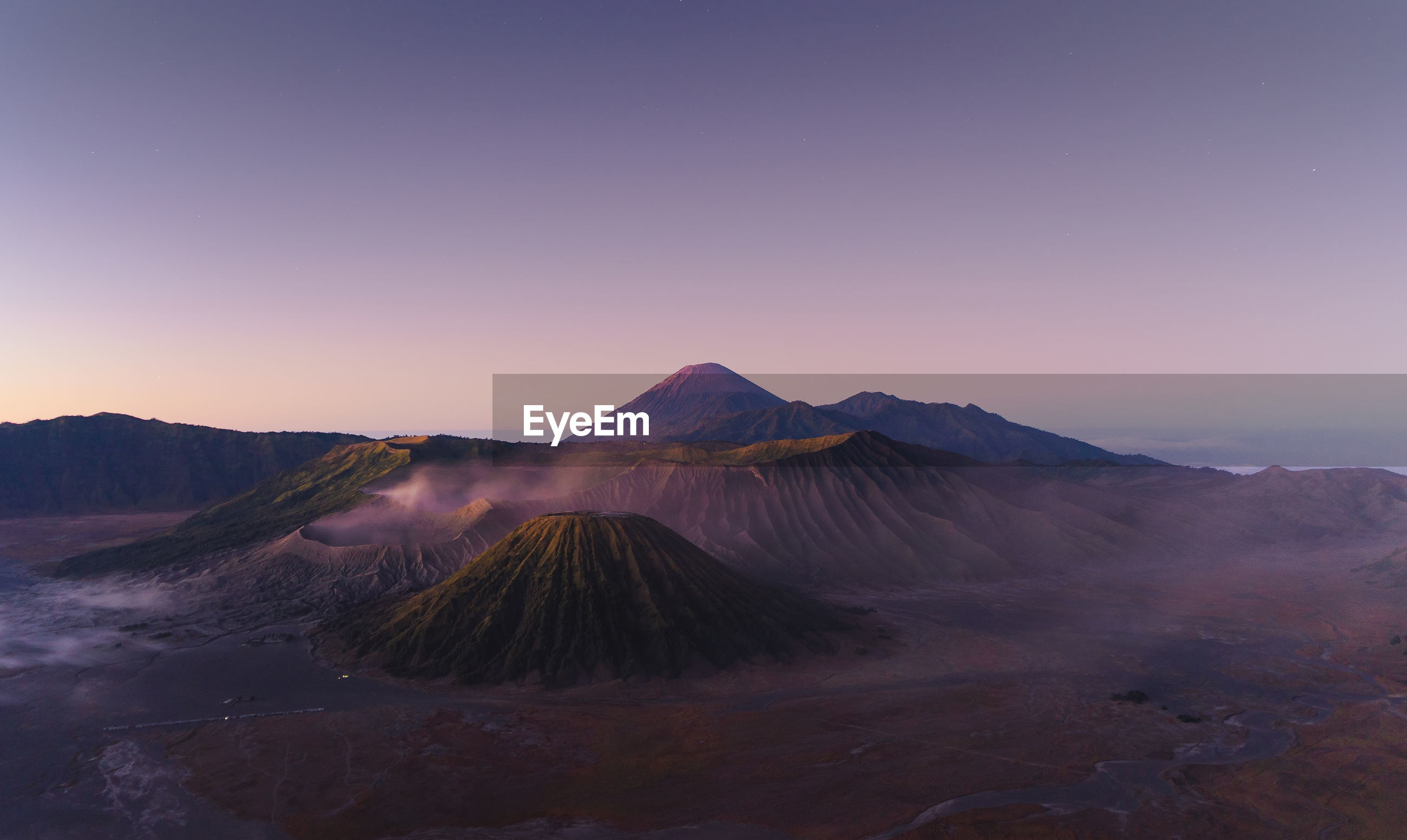 Scenic view of volcanoes against clear sky during sunset