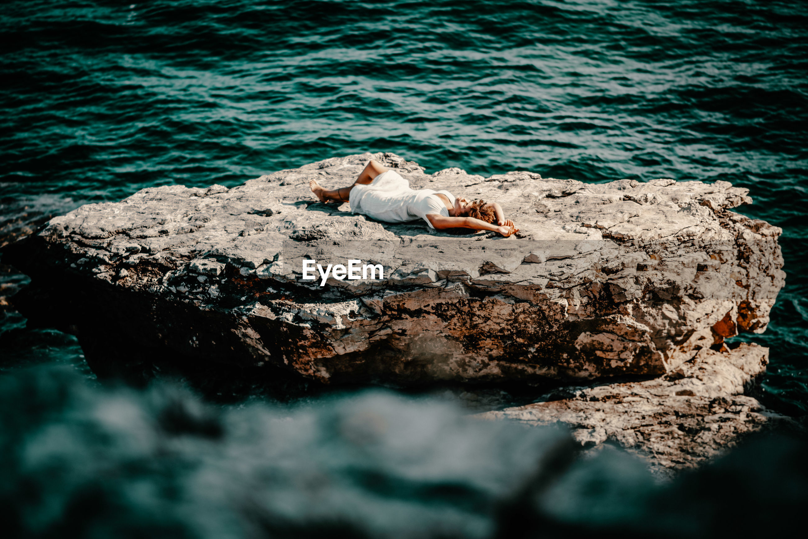 High angle view of woman lying cliff against sea
