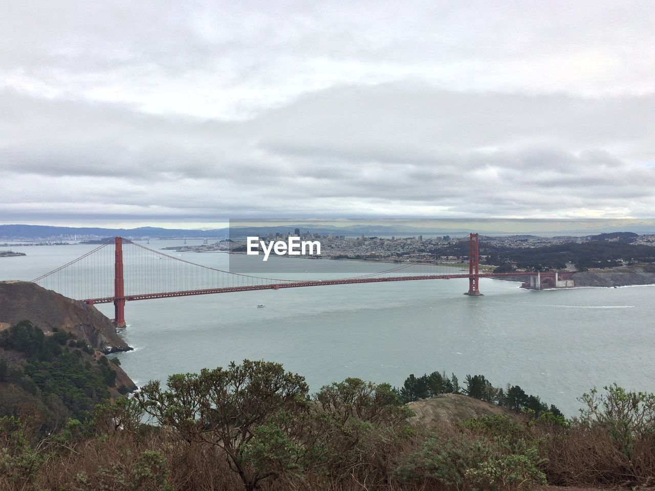 sky, connection, bridge - man made structure, suspension bridge, architecture, travel destinations, cloud - sky, mountain, water, built structure, day, nature, tourism, travel, scenics, outdoors, sea, no people, transportation, tranquil scene, tranquility, bridge, landscape, beauty in nature, city, tree, cityscape