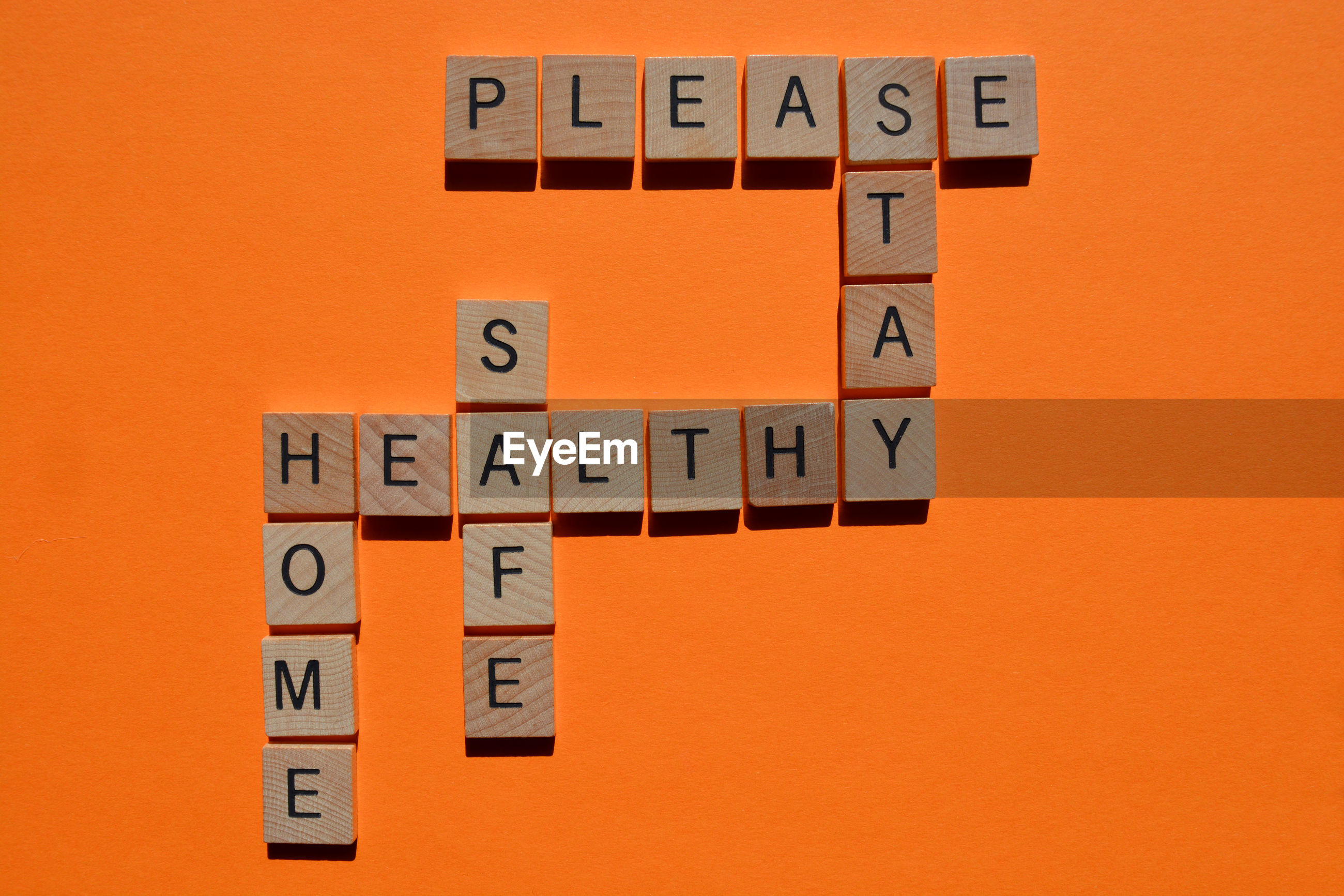 Please, stay, home, safe, healthy, crossword in 3d wooden alphabet letters on orange background