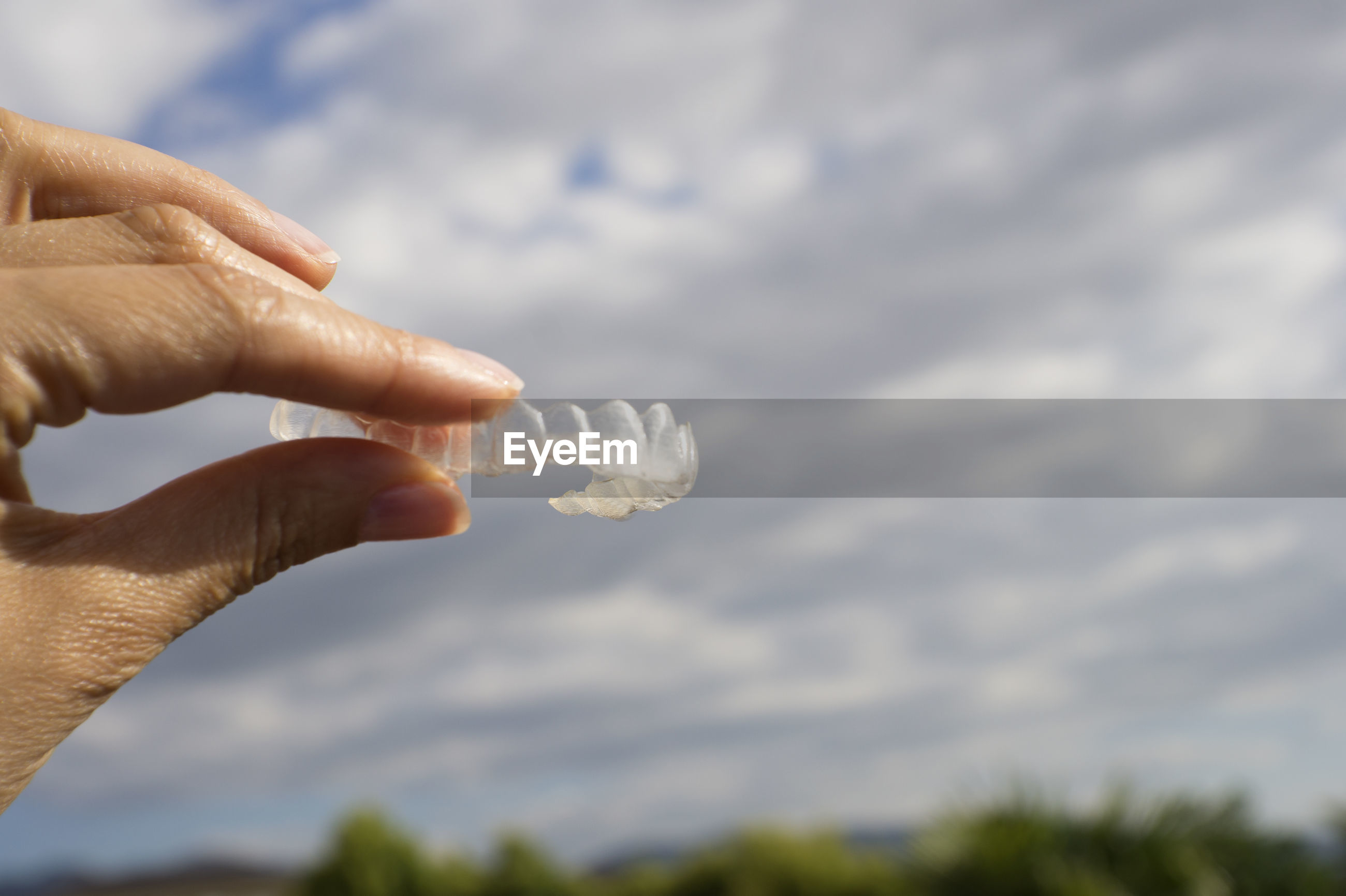 Cropped hands of person holding dentures against sky