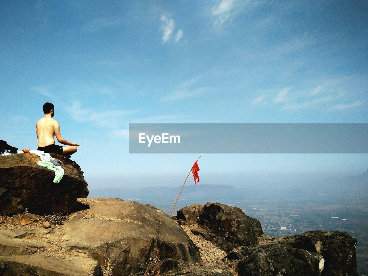 Shirtless Meditating On Rocky Landscape Against Blue Sky