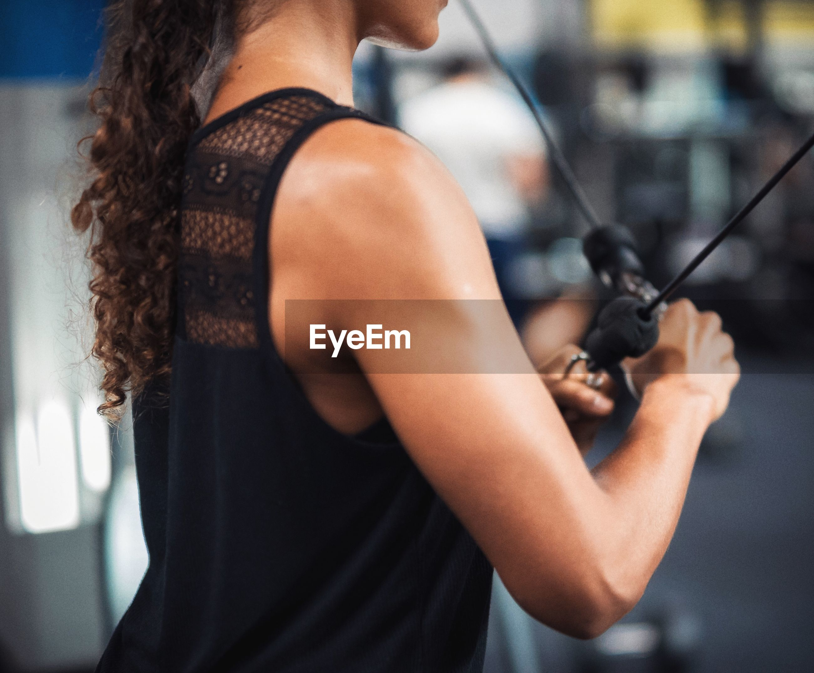 Midsection young woman exercising in gym
