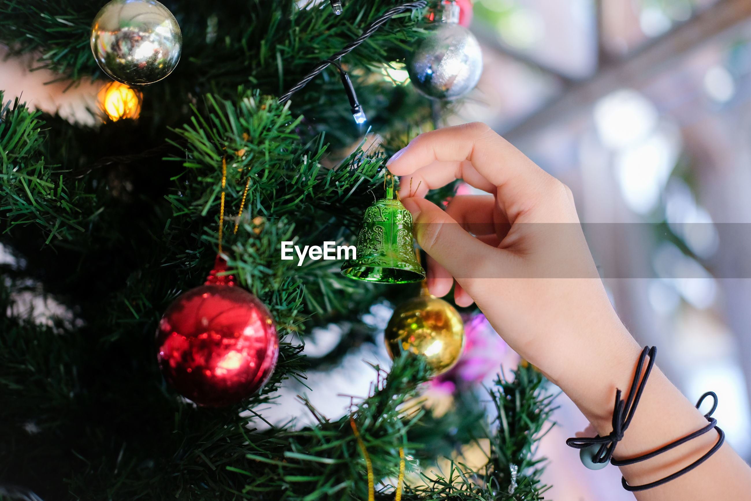 The hand of the girl decorating the christmas tree
