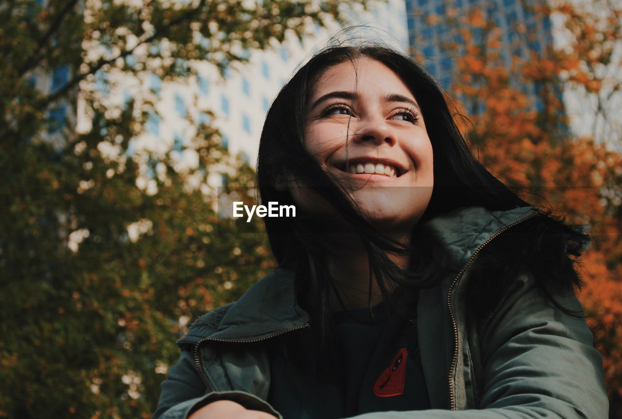 real people, autumn, one person, leisure activity, smiling, lifestyles, tree, leaf, nature, front view, outdoors, day, young women, headshot, focus on foreground, looking at camera, jacket, change, long hair, young adult, portrait, happiness, beautiful woman, beauty in nature, close-up, warm clothing, people