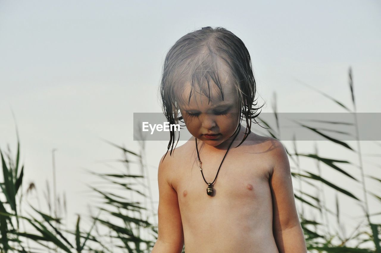 Portrait Of Shirtless Boy Against Sky