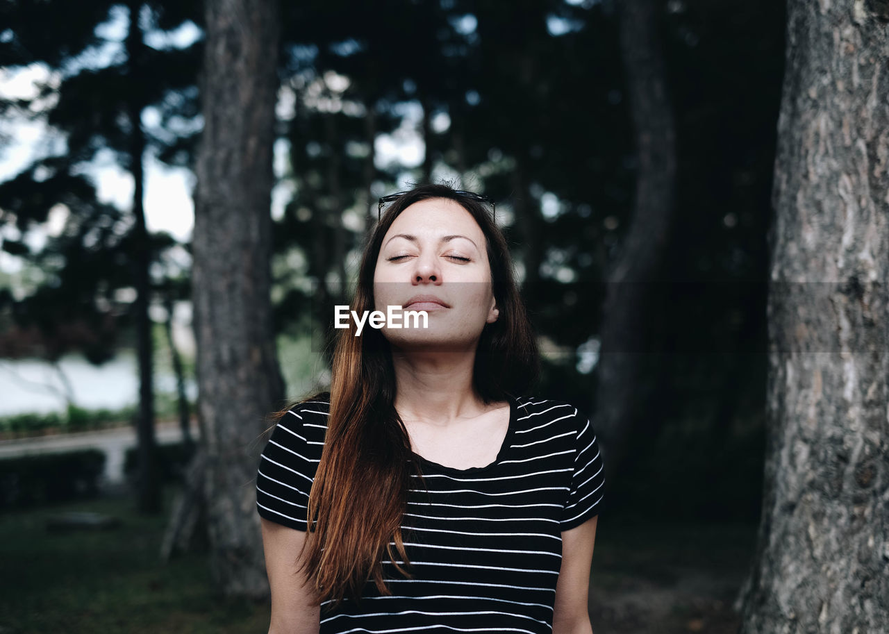 Woman with closed eyes against trees