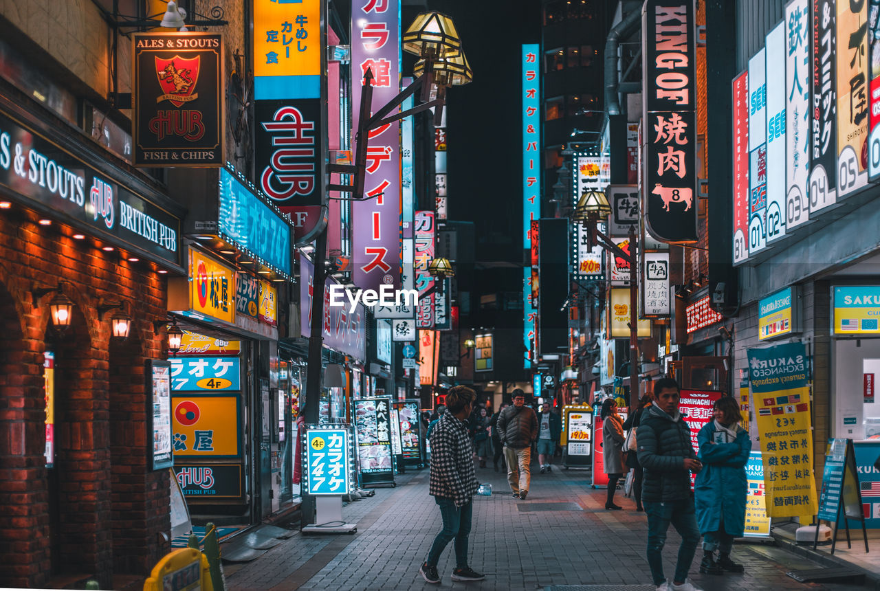 architecture, city, building exterior, illuminated, built structure, night, city life, real people, street, group of people, walking, text, communication, non-western script, advertisement, script, building, sign, commercial sign, neon, city street, outdoors