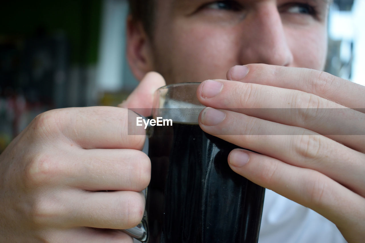 Close-Up Of Man Drinking Black Coffee At Cafe