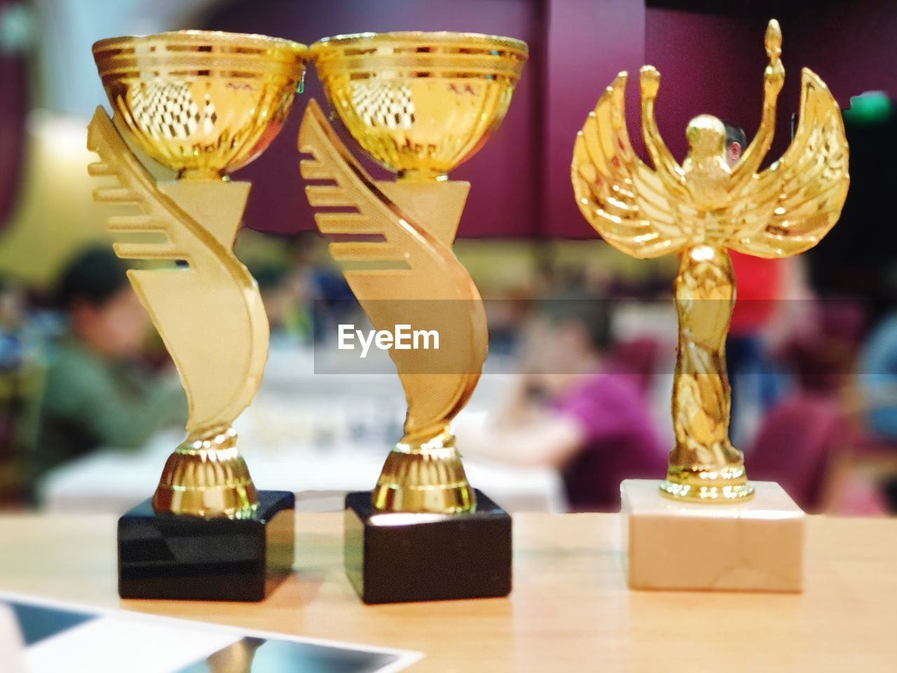 gold colored, close-up, focus on foreground, indoors, table, no people, still life, award, trophy, art and craft, creativity, in a row, arrangement, selective focus, representation, shiny, sculpture, statue, group of objects, achievement