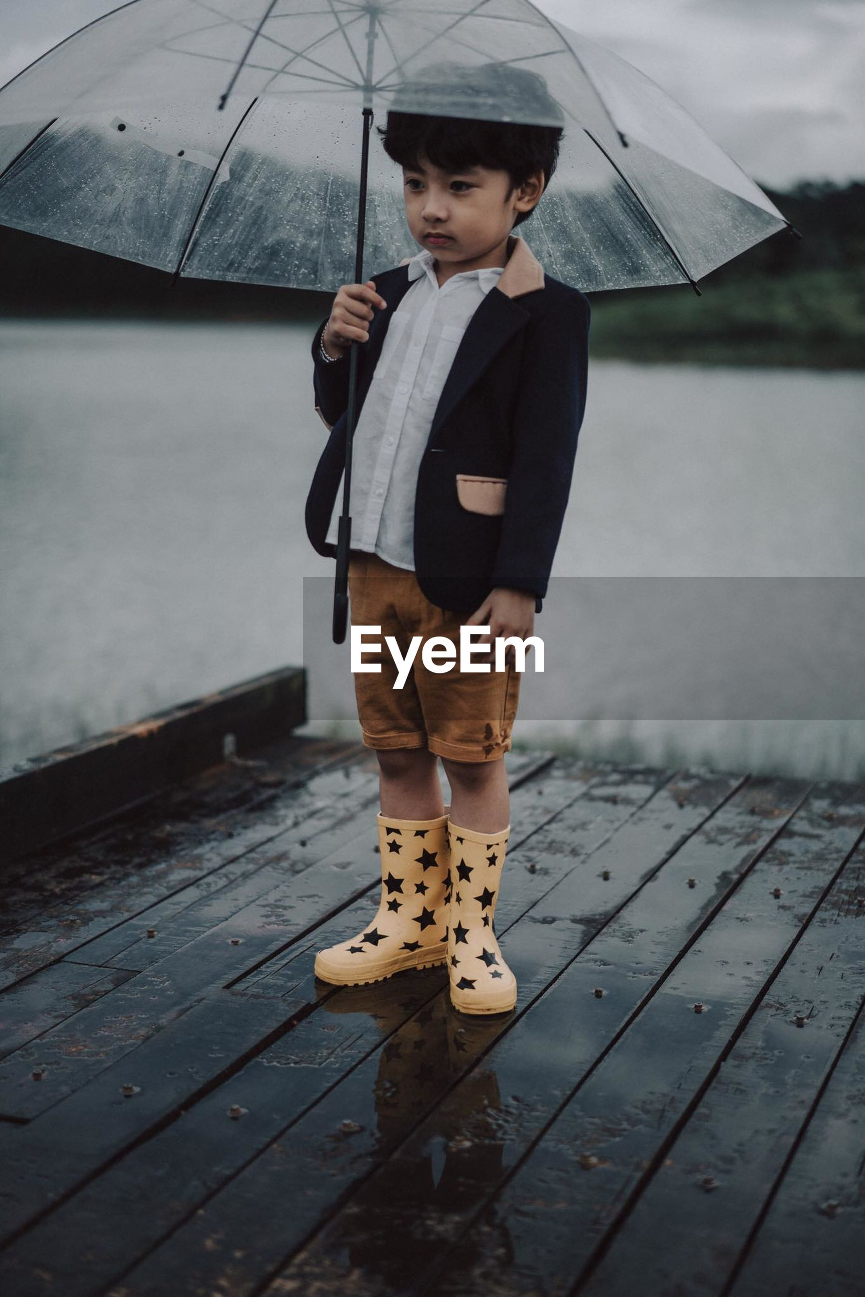 Boy with umbrella standing on pier against lake during rainfall