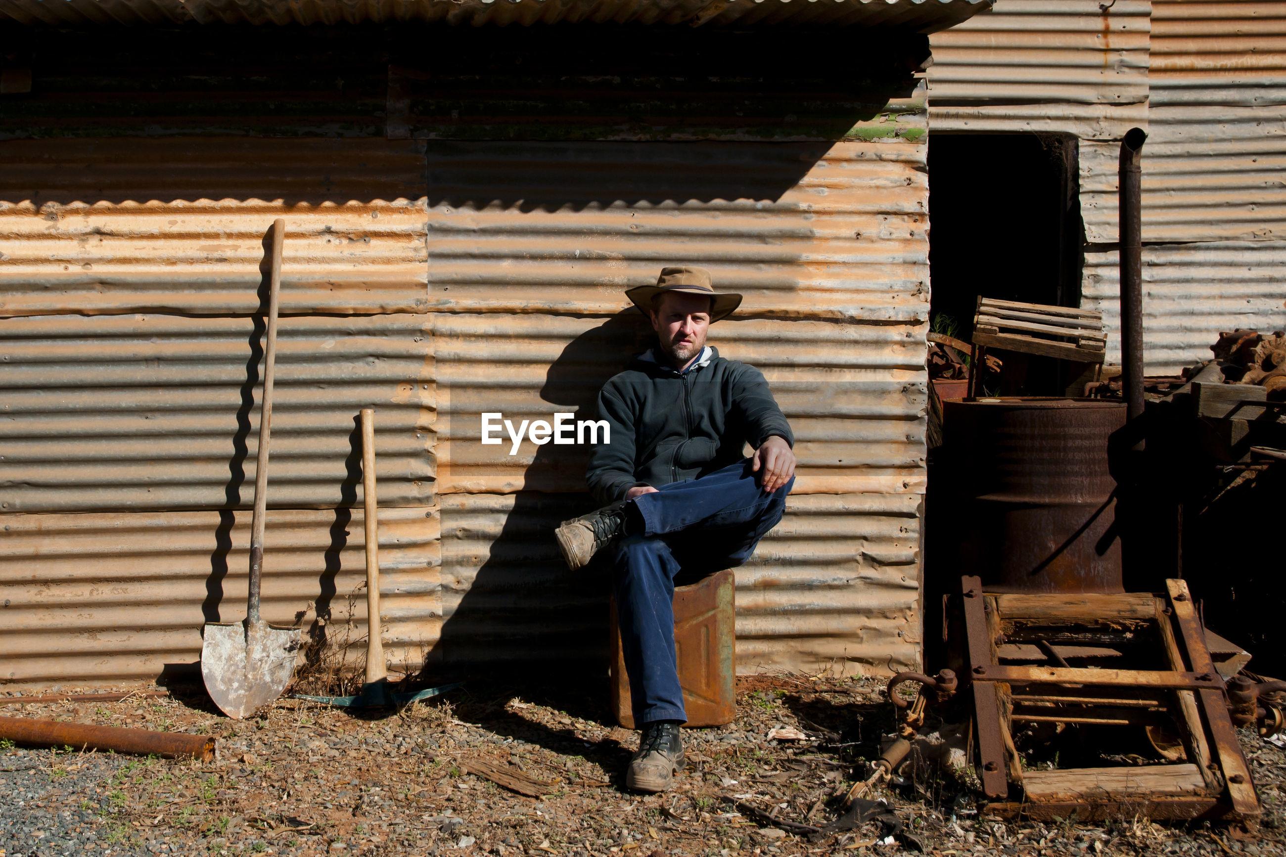 Men sitting against barn