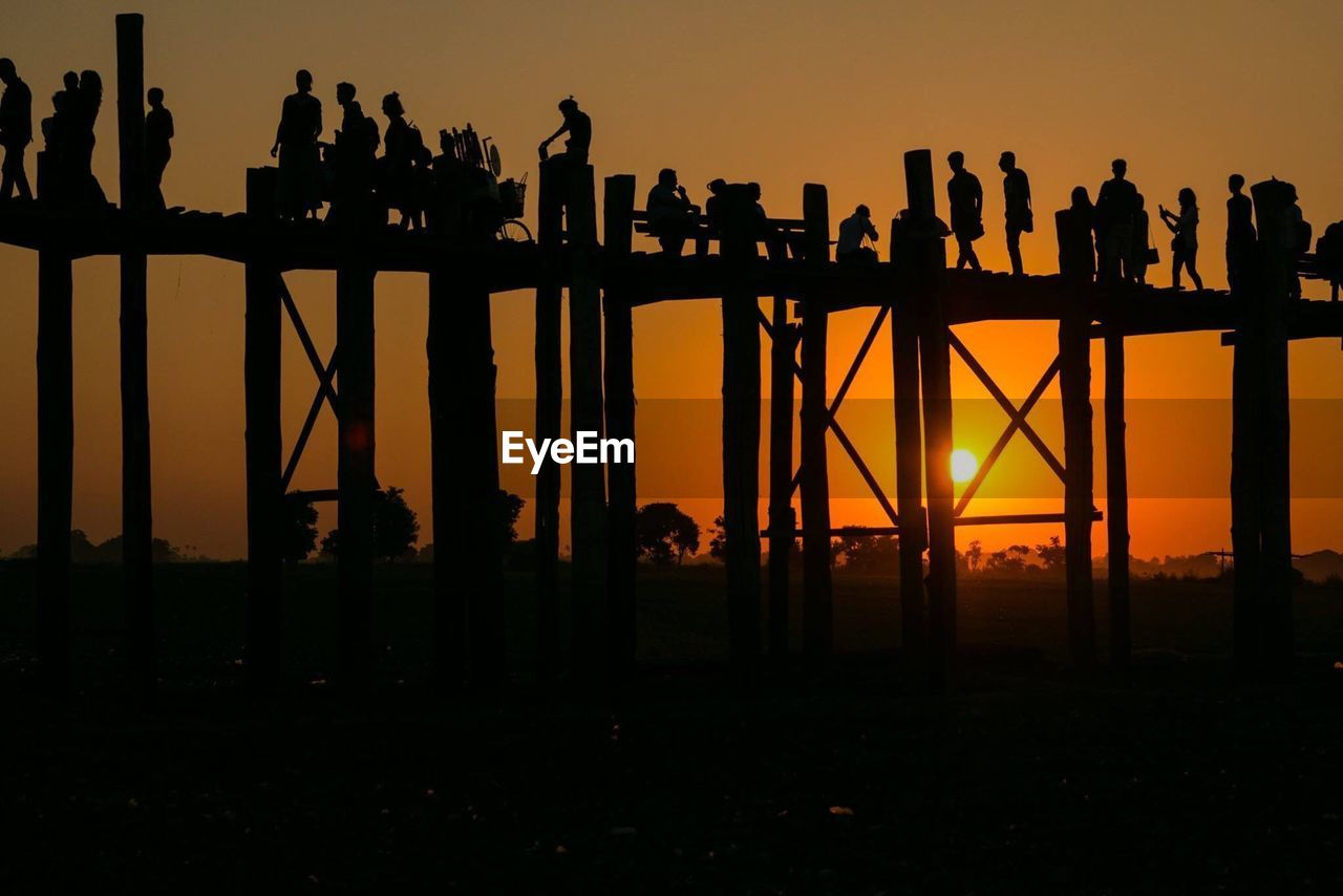 silhouette, sunset, sky, orange color, group of people, nature, built structure, architecture, men, real people, sun, outdoors, beauty in nature, scenics - nature, bridge, connection, people, leisure activity, outline, standing