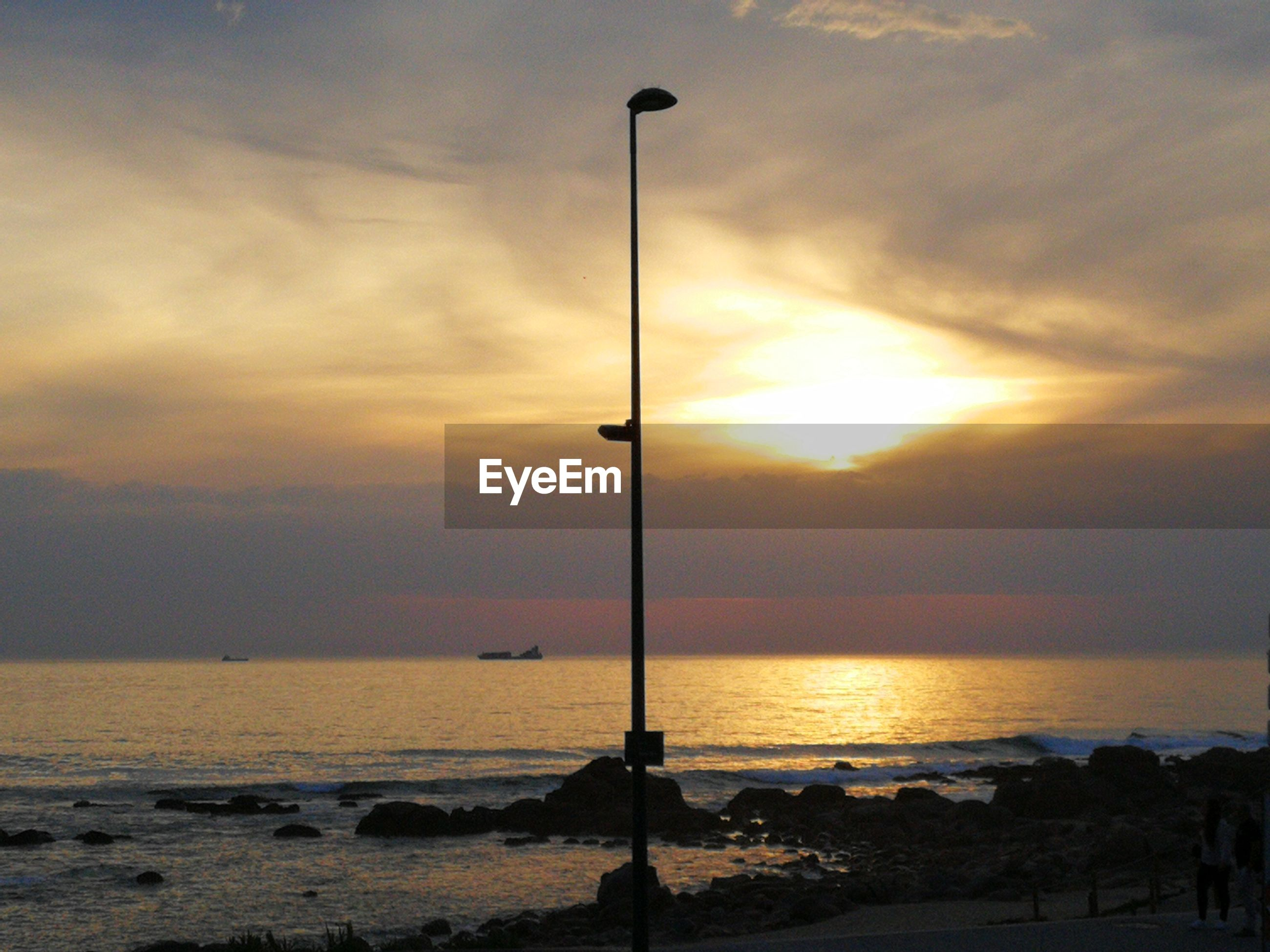 SILHOUETTE STREET LIGHT ON BEACH DURING SUNSET