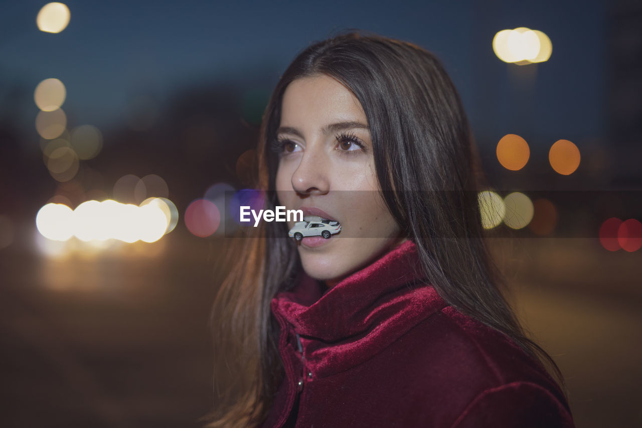 headshot, one person, portrait, young adult, focus on foreground, lifestyles, young women, leisure activity, illuminated, real people, night, women, beauty, beautiful woman, looking away, long hair, hairstyle, hair, looking, lens flare, contemplation, scarf
