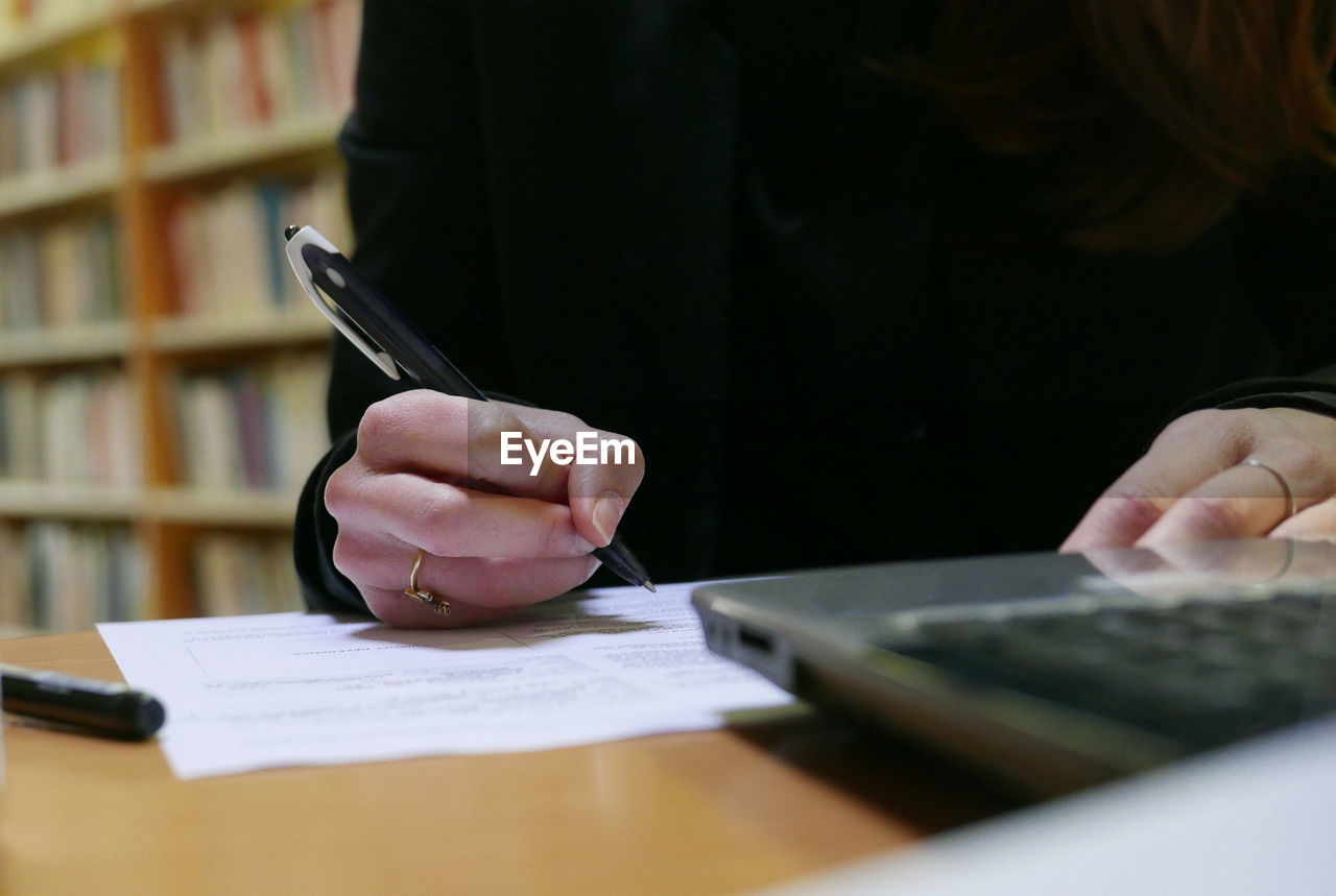 Midsection of young woman holding pen in library