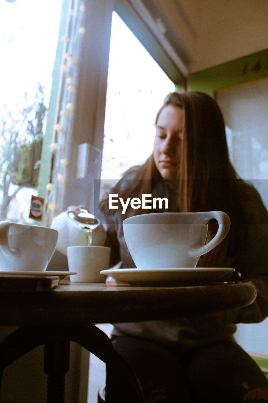 Low angle view of young woman having coffee at table in cafe