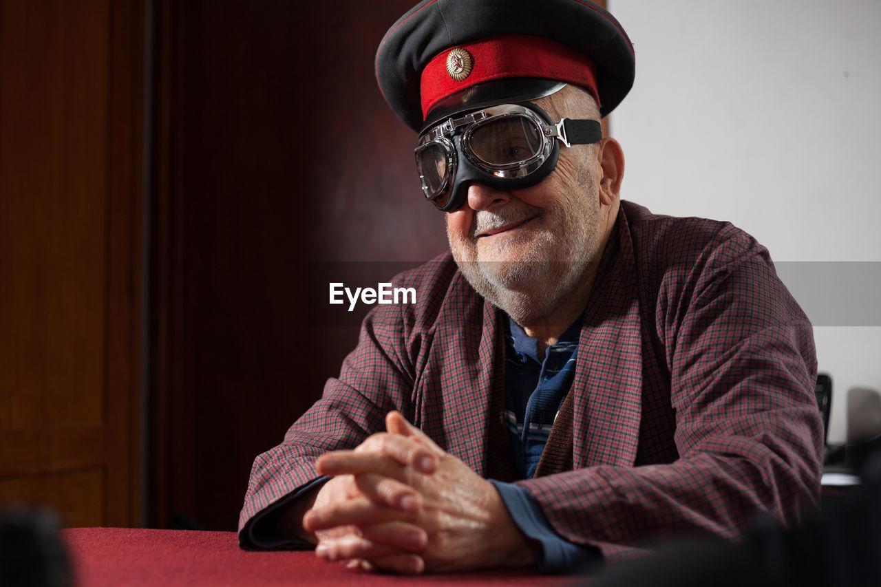 Smiling senior man wearing aviator glasses and cap