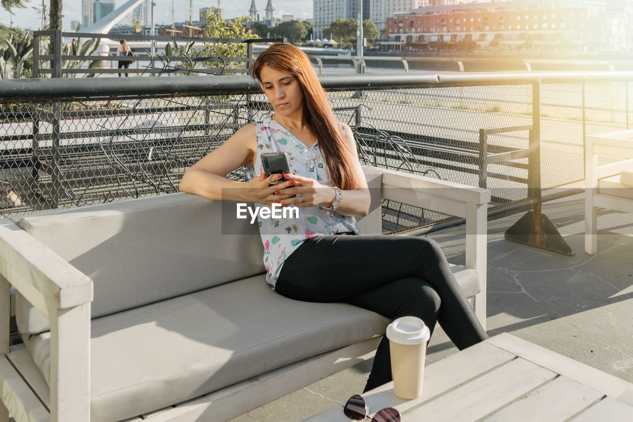 FULL LENGTH OF WOMAN USING MOBILE PHONE WHILE SITTING ON CAMERA AT SMART