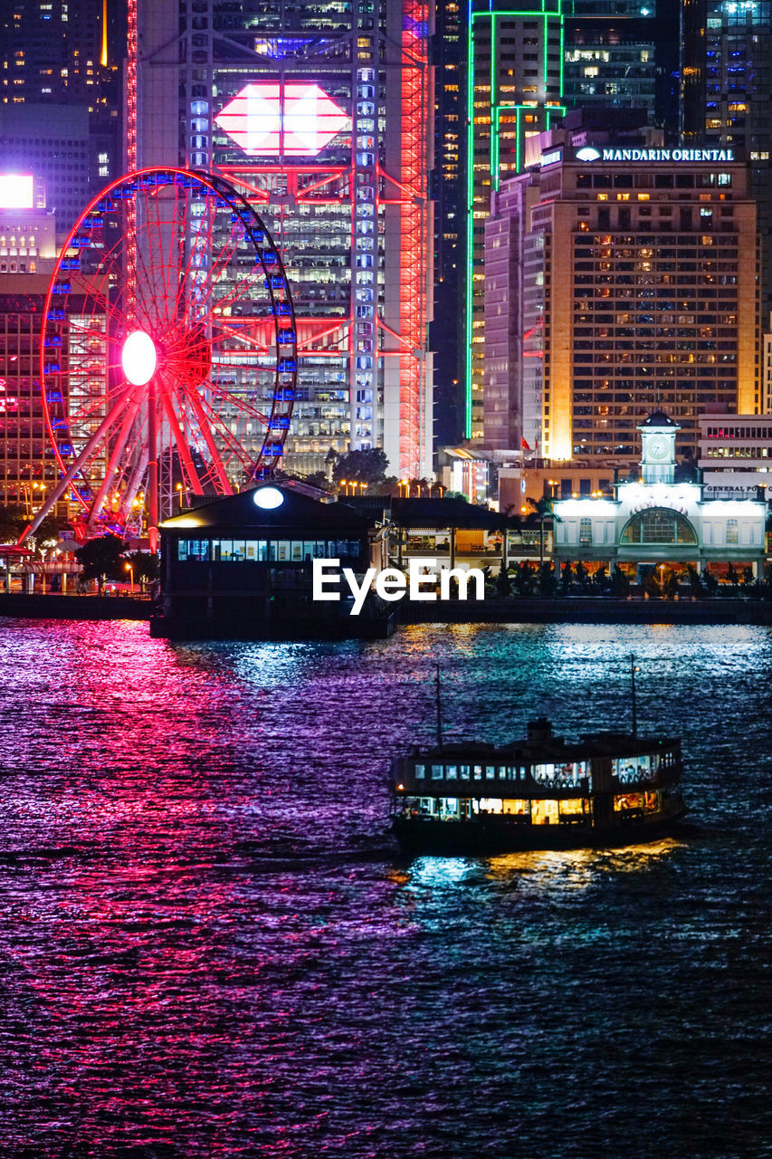 illuminated, water, building exterior, architecture, built structure, waterfront, city, night, no people, nautical vessel, reflection, transportation, building, office building exterior, outdoors, river, arts culture and entertainment, amusement park, urban skyline, skyscraper, modern, cityscape, light, financial district, nightlife