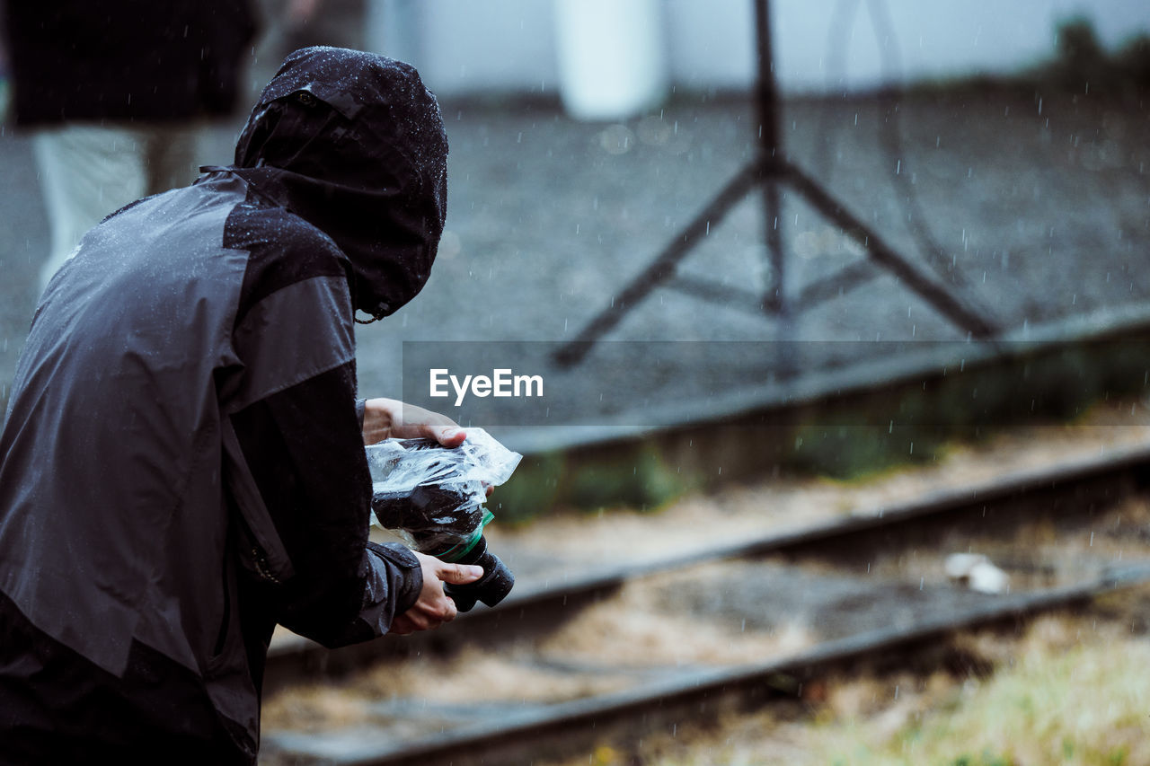Side View Of Man Photographing With Camera While Standing Outdoors During Rainfall