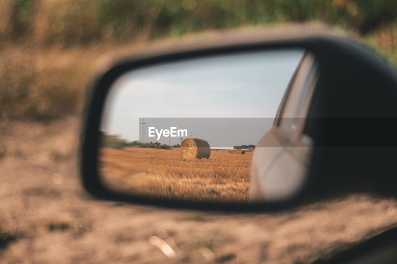 land vehicle, motor vehicle, mode of transportation, selective focus, car, transportation, land, side-view mirror, field, glass - material, reflection, nature, no people, day, close-up, sky, mirror, rear-view mirror, road, outdoors