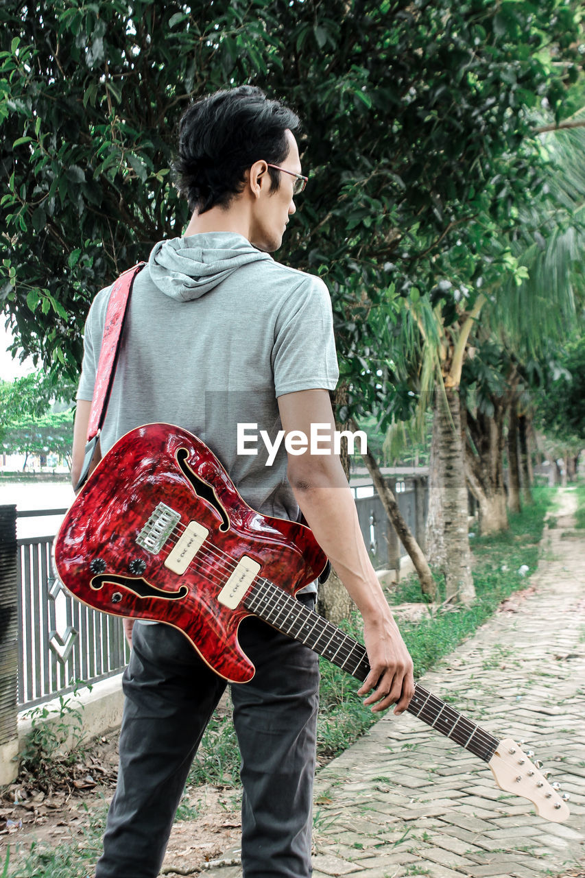 YOUNG MAN HOLDING GUITAR WHILE STANDING BY PLANT