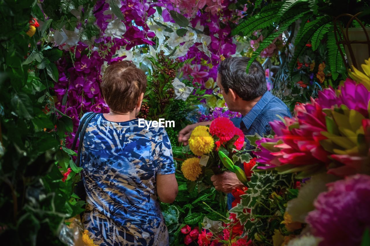 flower, flowering plant, plant, men, two people, real people, child, nature, childhood, leisure activity, males, togetherness, growth, boys, day, freshness, rear view, lifestyles, women, bouquet, flower arrangement, outdoors, flower head