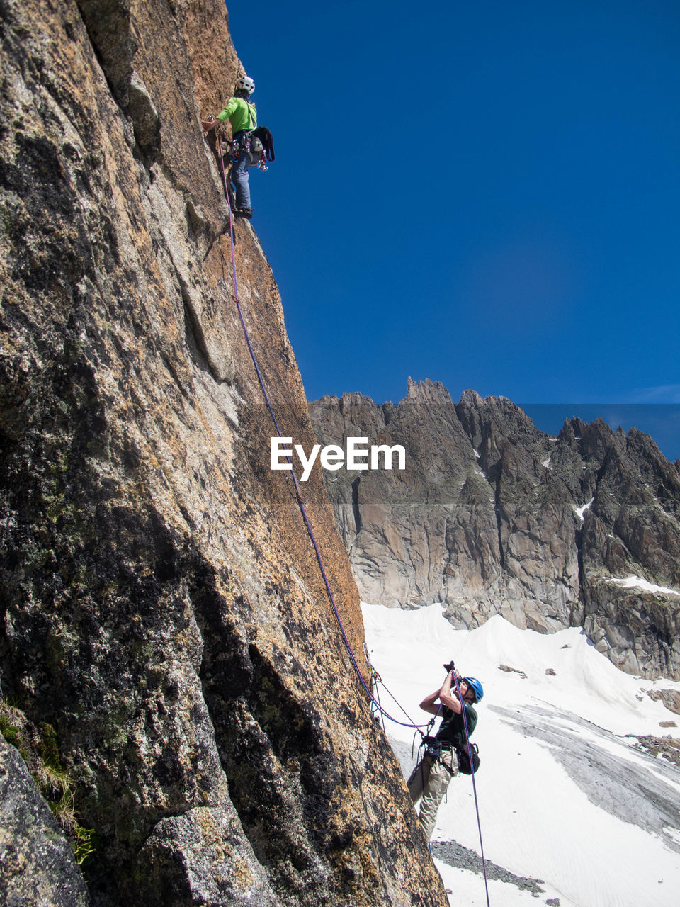 adventure, rock - object, rock climbing, real people, rope, climbing, risk, low angle view, mountain, men, leisure activity, day, skill, extreme sports, lifestyles, vitality, full length, cliff, healthy lifestyle, young men, outdoors, helmet, courage, climbing rope, challenge, sport, young adult, nature, rock face, clear sky, headwear, only men, adult, sky, adults only, people
