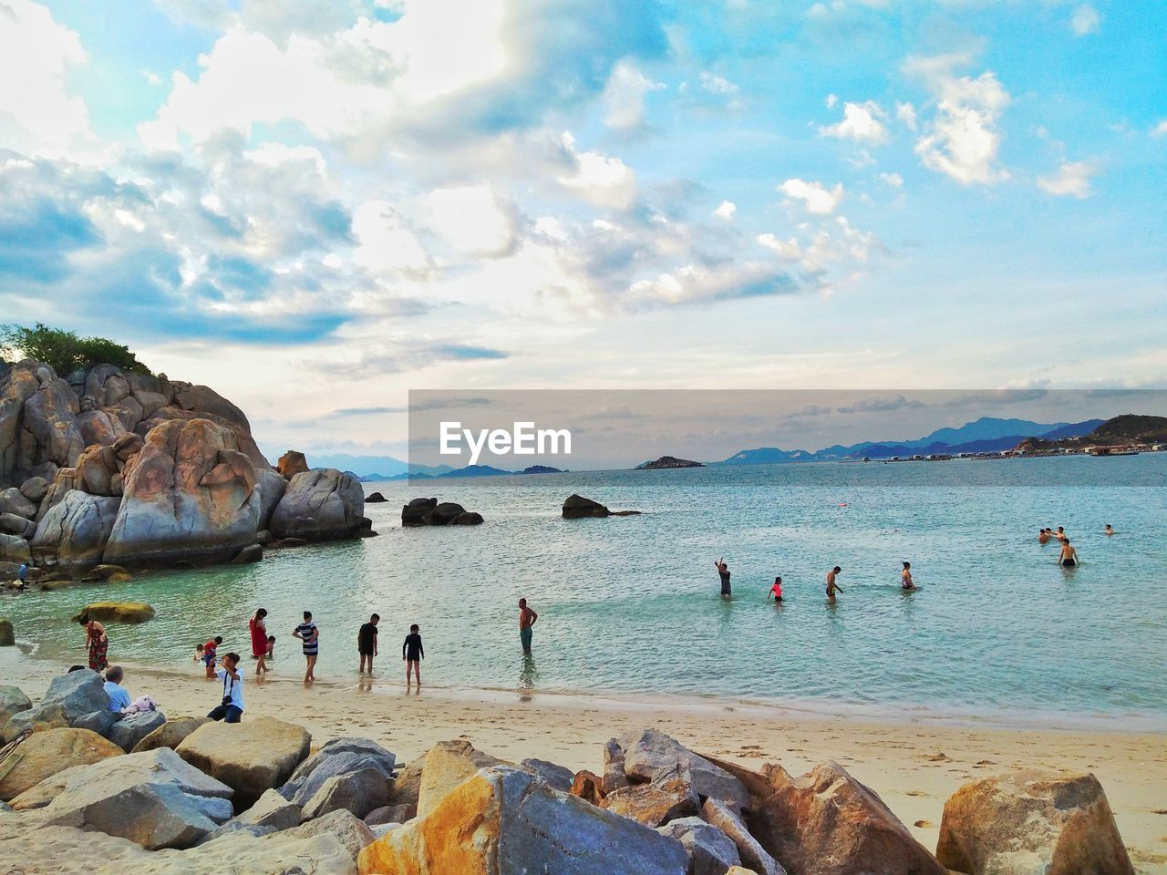 water, sea, group of people, beach, sky, land, cloud - sky, rock, crowd, leisure activity, large group of people, real people, lifestyles, holiday, vacations, trip, nature, solid, rock - object, outdoors