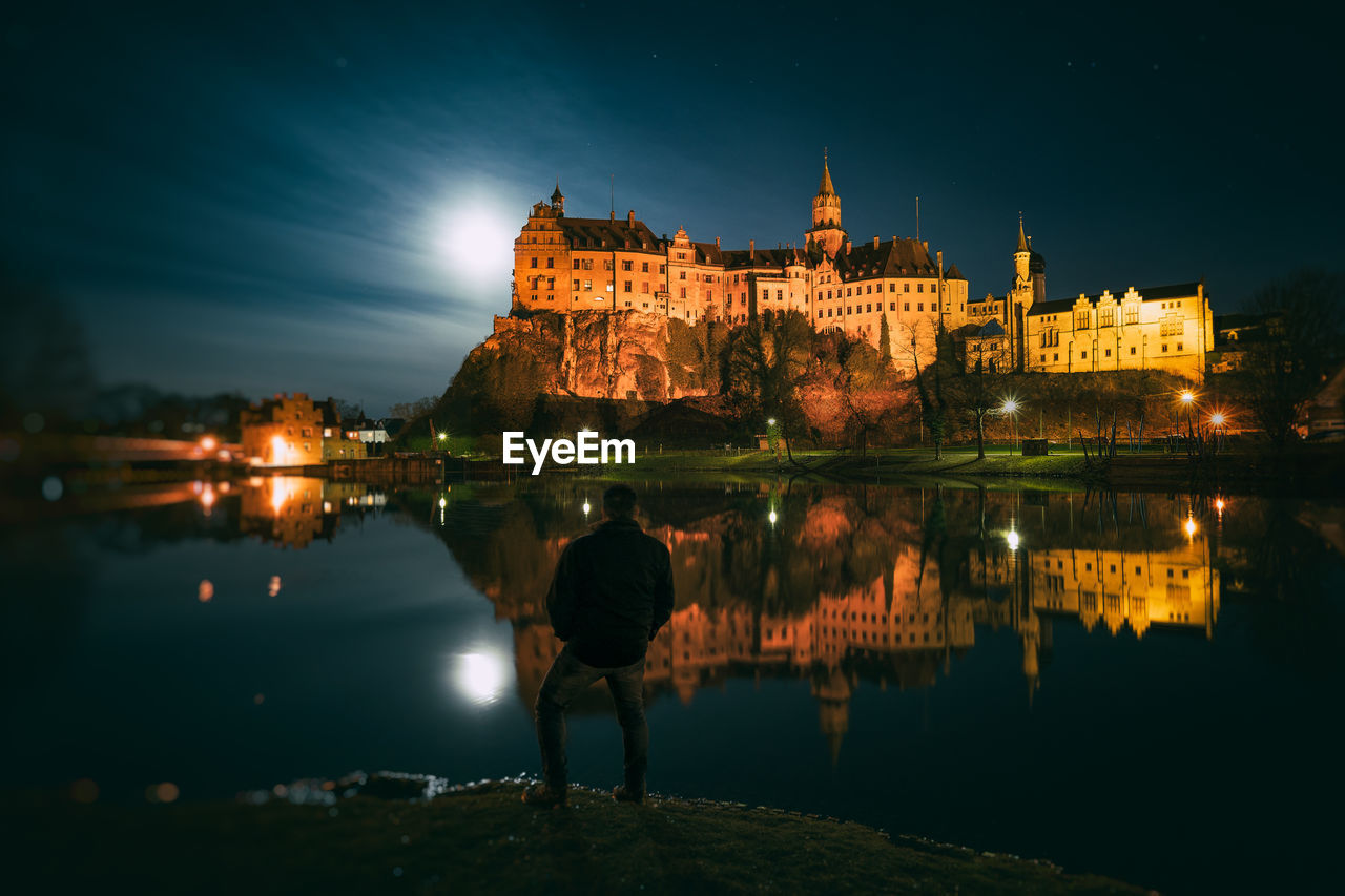 water, building exterior, architecture, built structure, sky, illuminated, reflection, night, nature, real people, lifestyles, building, lake, people, rear view, leisure activity, castle, travel destinations, outdoors