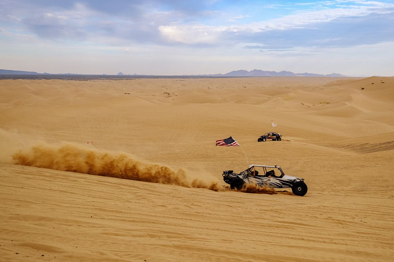 Cars In Desert Against Sky