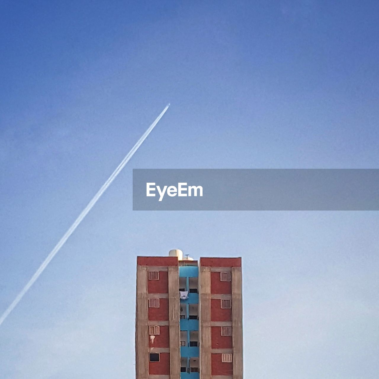 Low angle view of vapor trail and residential building against clear blue sky