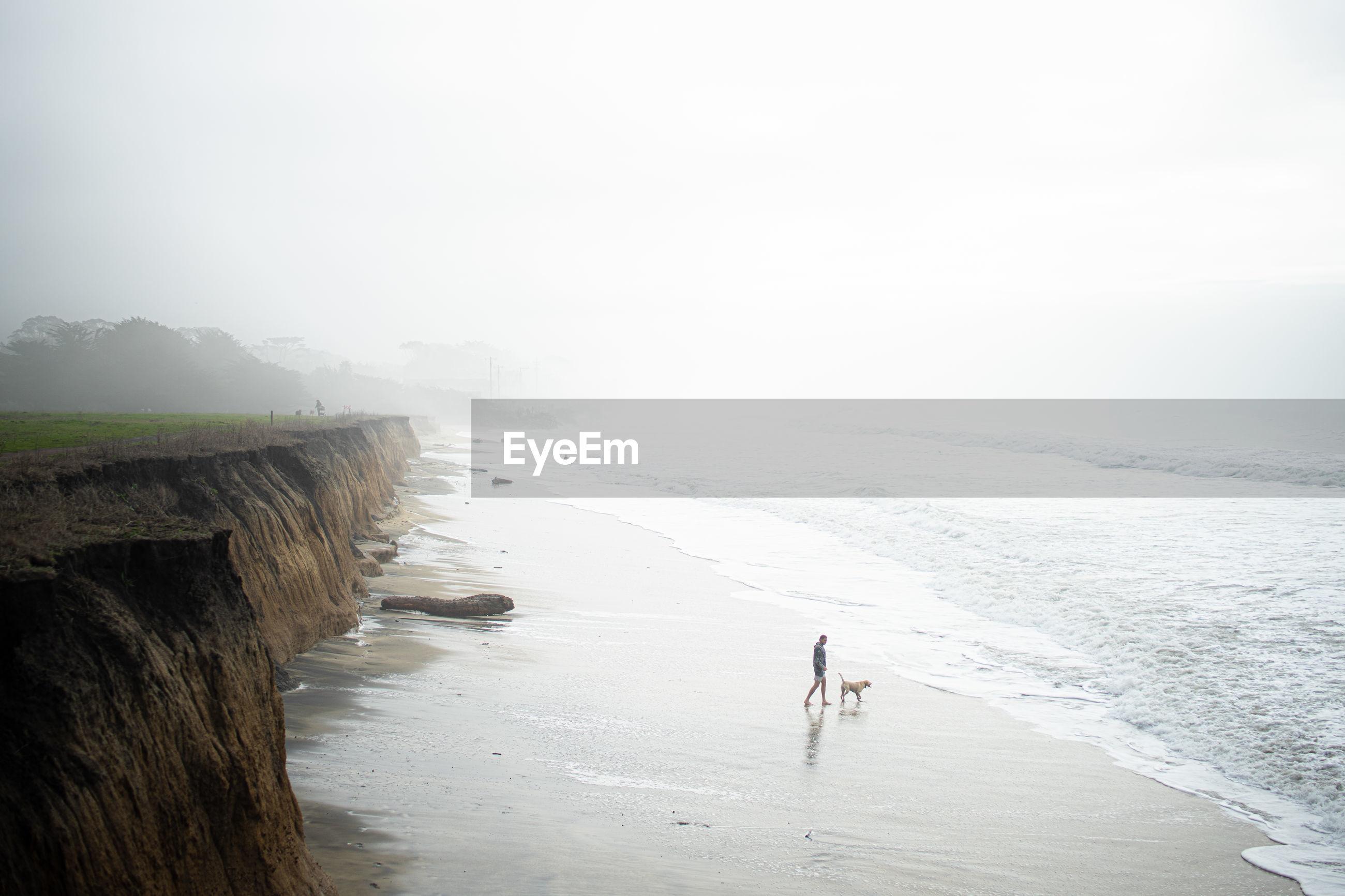 MEN WALKING ON BEACH AGAINST SKY