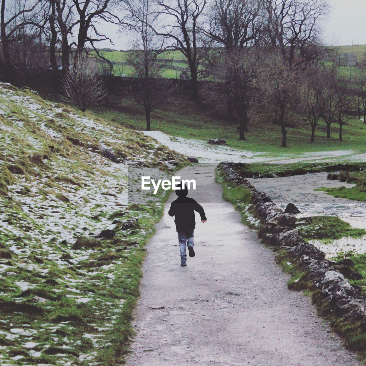 Boy running on footpath amidst snow covered field at park