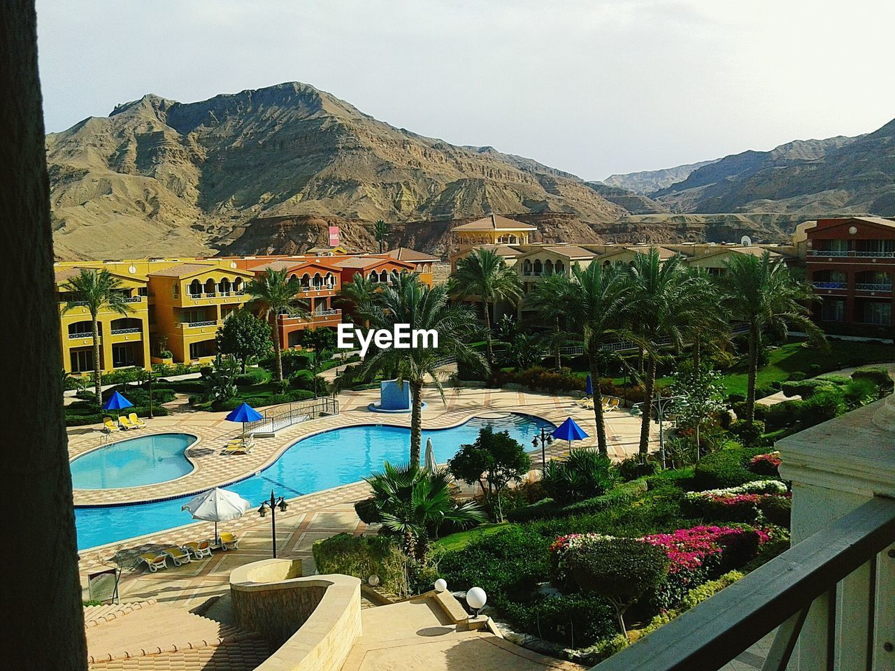 mountain, swimming pool, mountain range, water, day, nature, built structure, tree, high angle view, outdoors, no people, architecture, beauty in nature, building exterior, scenics, clear sky, sky