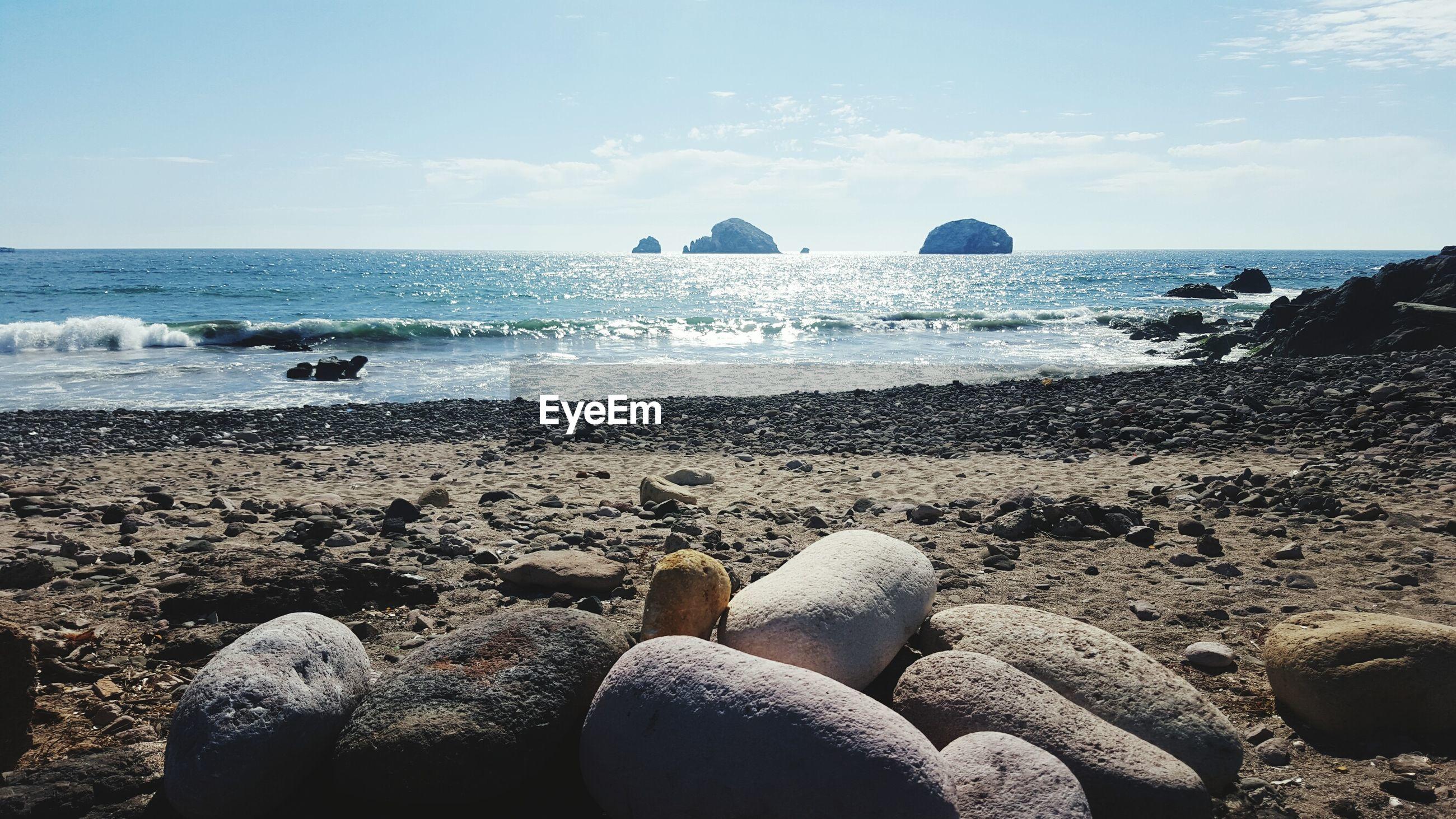 ROCKS AT BEACH AGAINST SKY