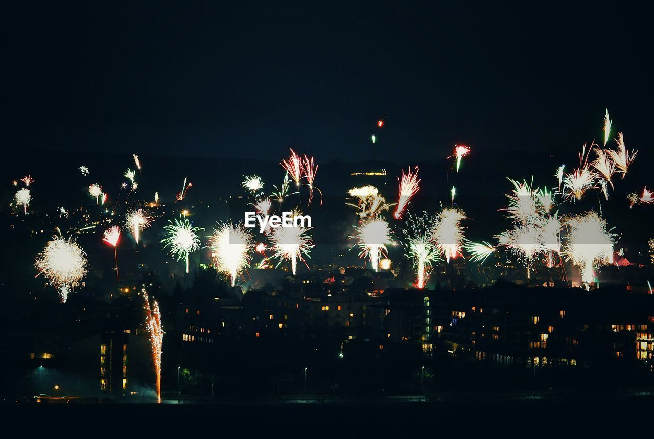 night, celebration, firework display, firework - man made object, illuminated, arts culture and entertainment, exploding, glowing, long exposure, sparks, blurred motion, event, outdoors, motion, low angle view, multi colored, sky, firework, no people, clear sky, city
