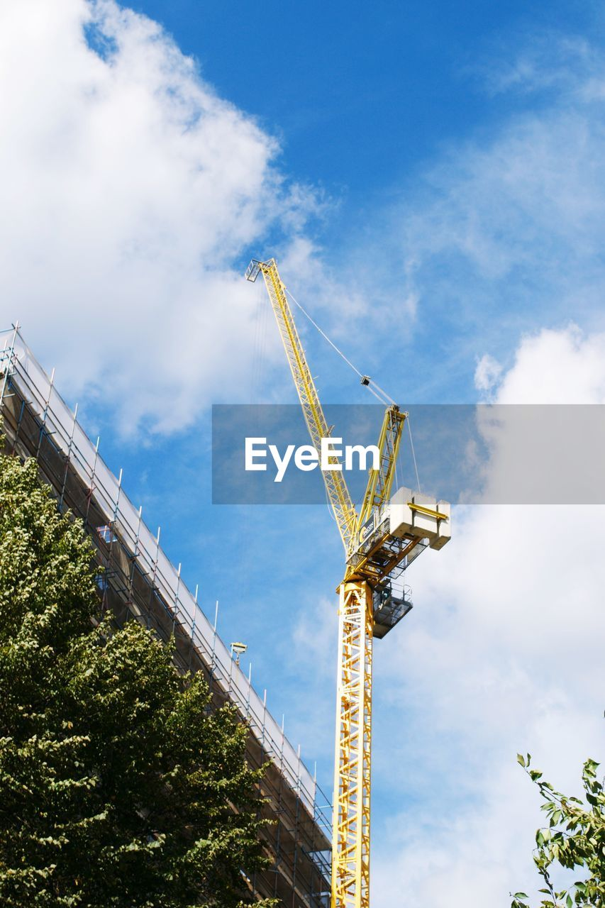low angle view, cloud - sky, sky, day, architecture, development, no people, blue, outdoors, built structure, construction site, growth, tree, building exterior, technology, nature