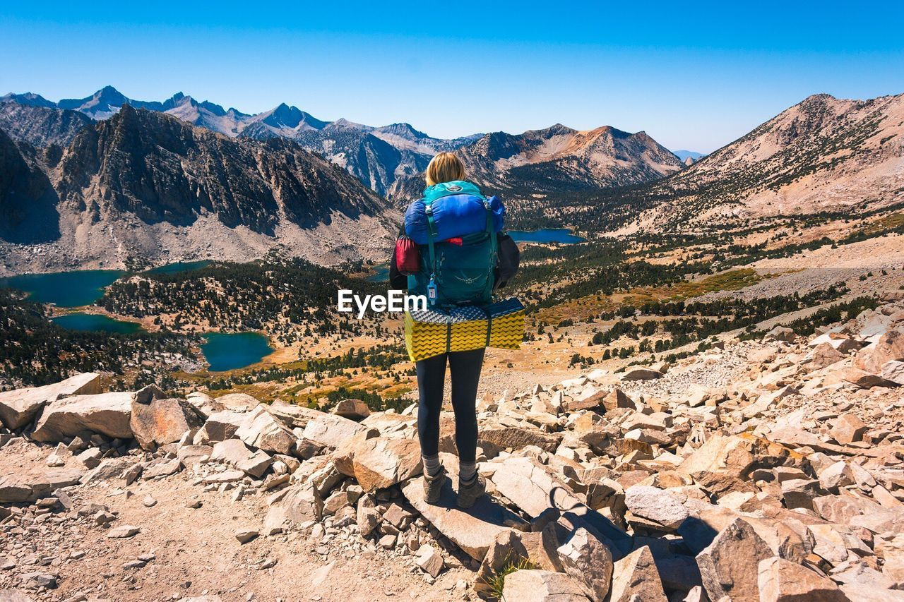 Rear View Of Woman Hiking On Mountain Against Clear Sky During Sunny Day