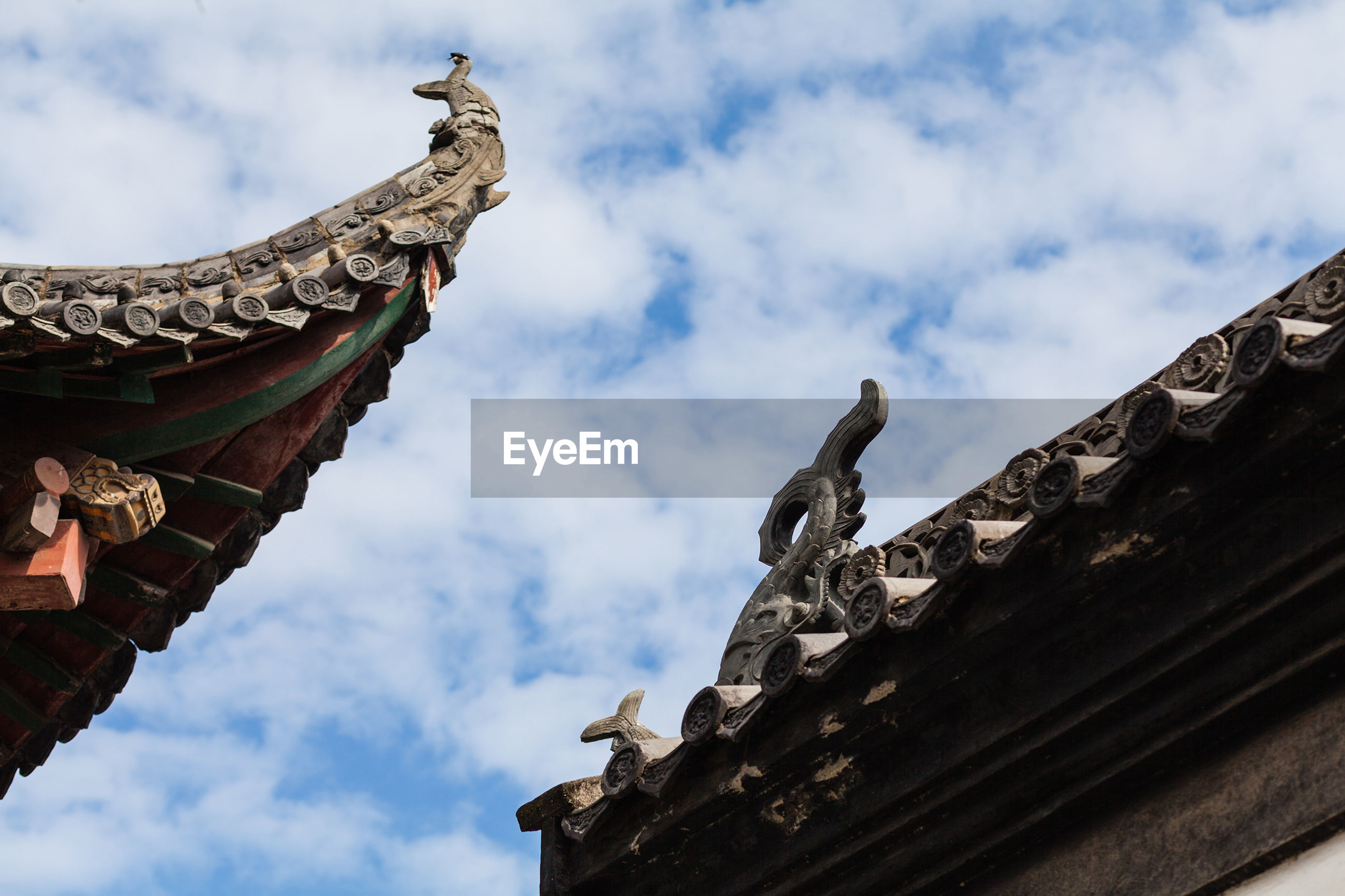 Low angle view of carvings on wooden buildings against cloudy sky