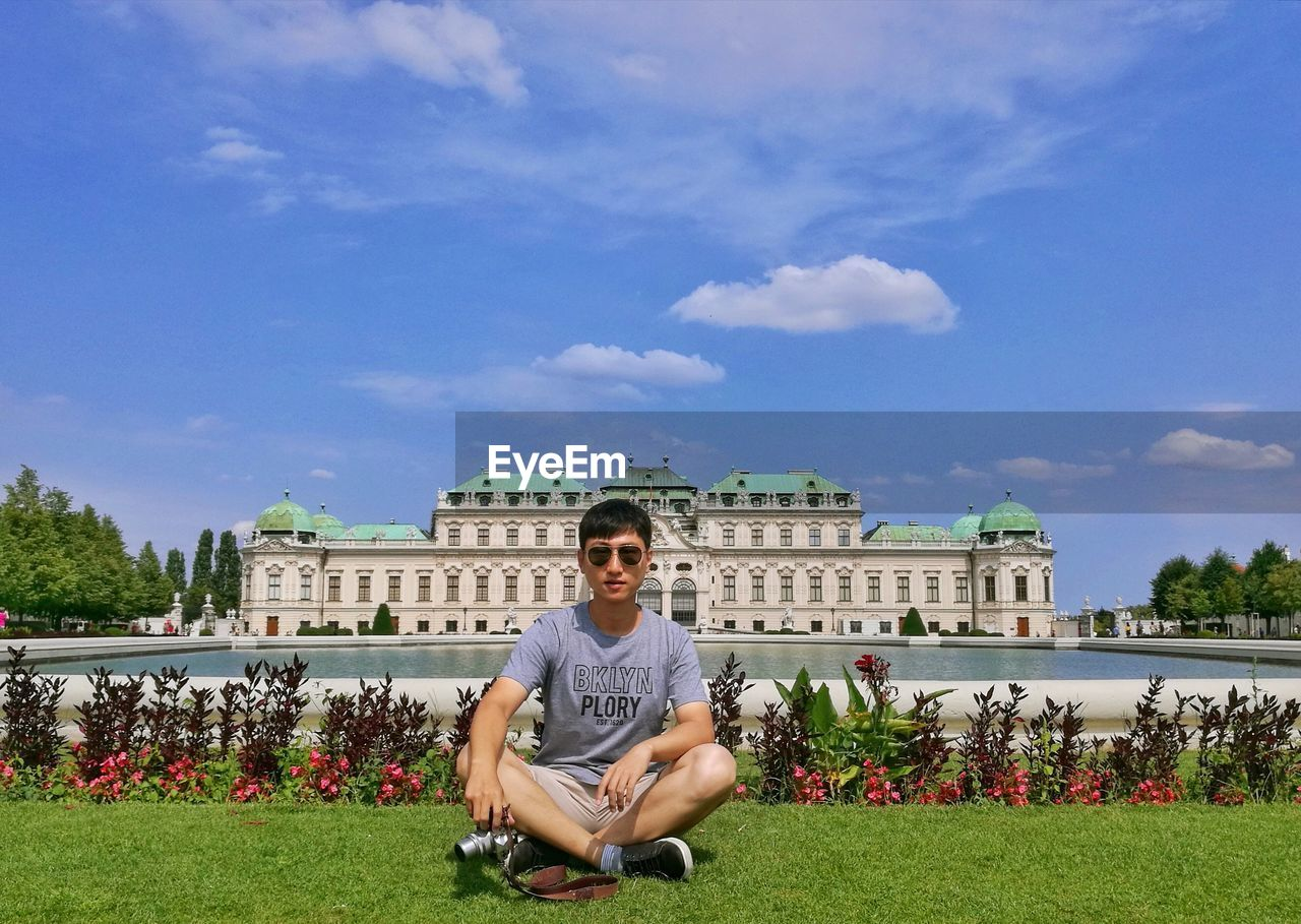 Portrait Of Young Man Sitting On Field Against Belvedere Palace