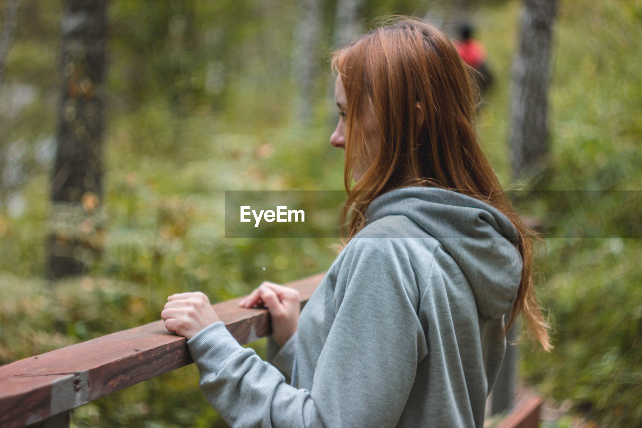 Woman smiling while standing at railing in forest