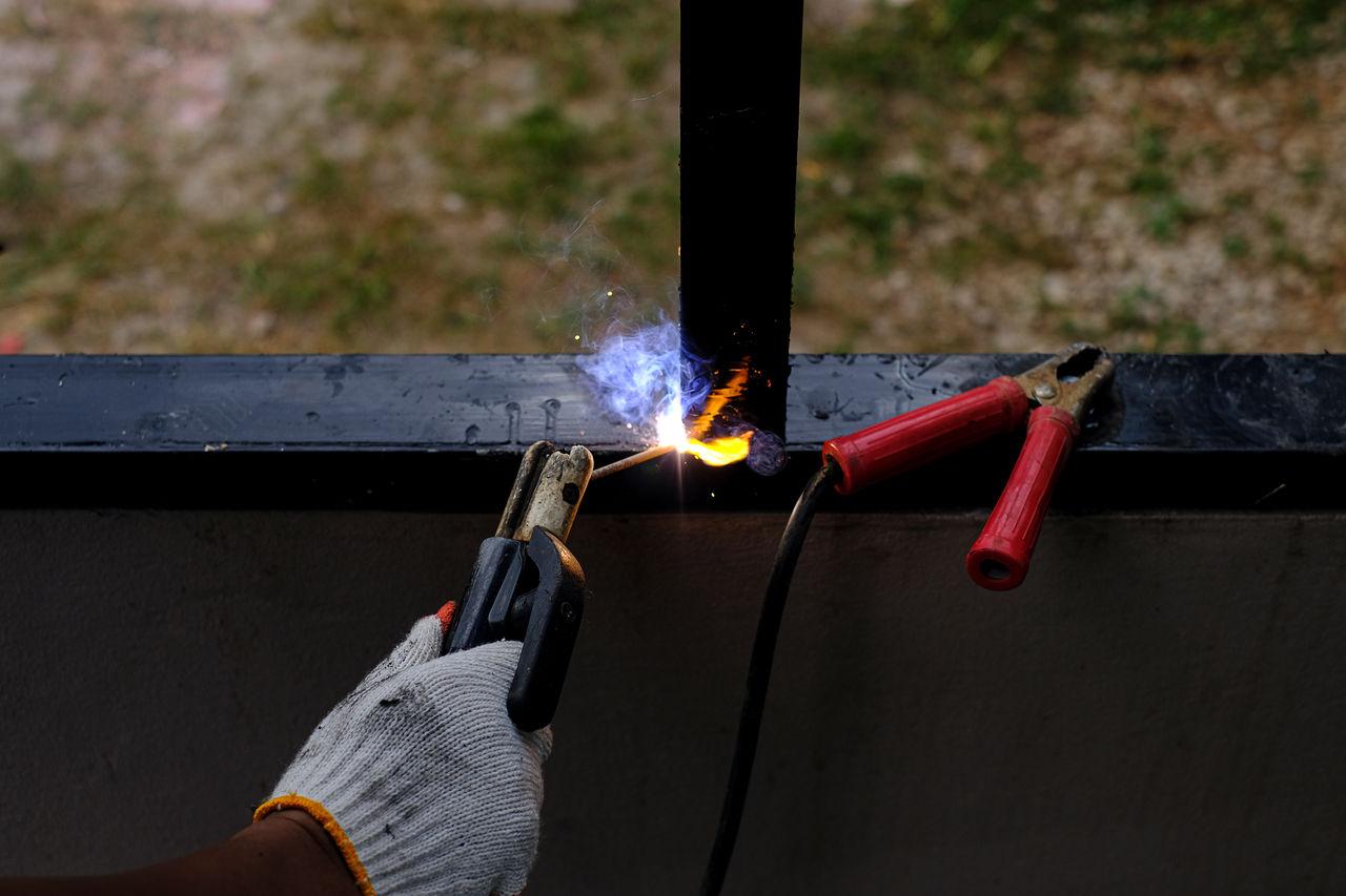 Cropped hand of welder welding window frame
