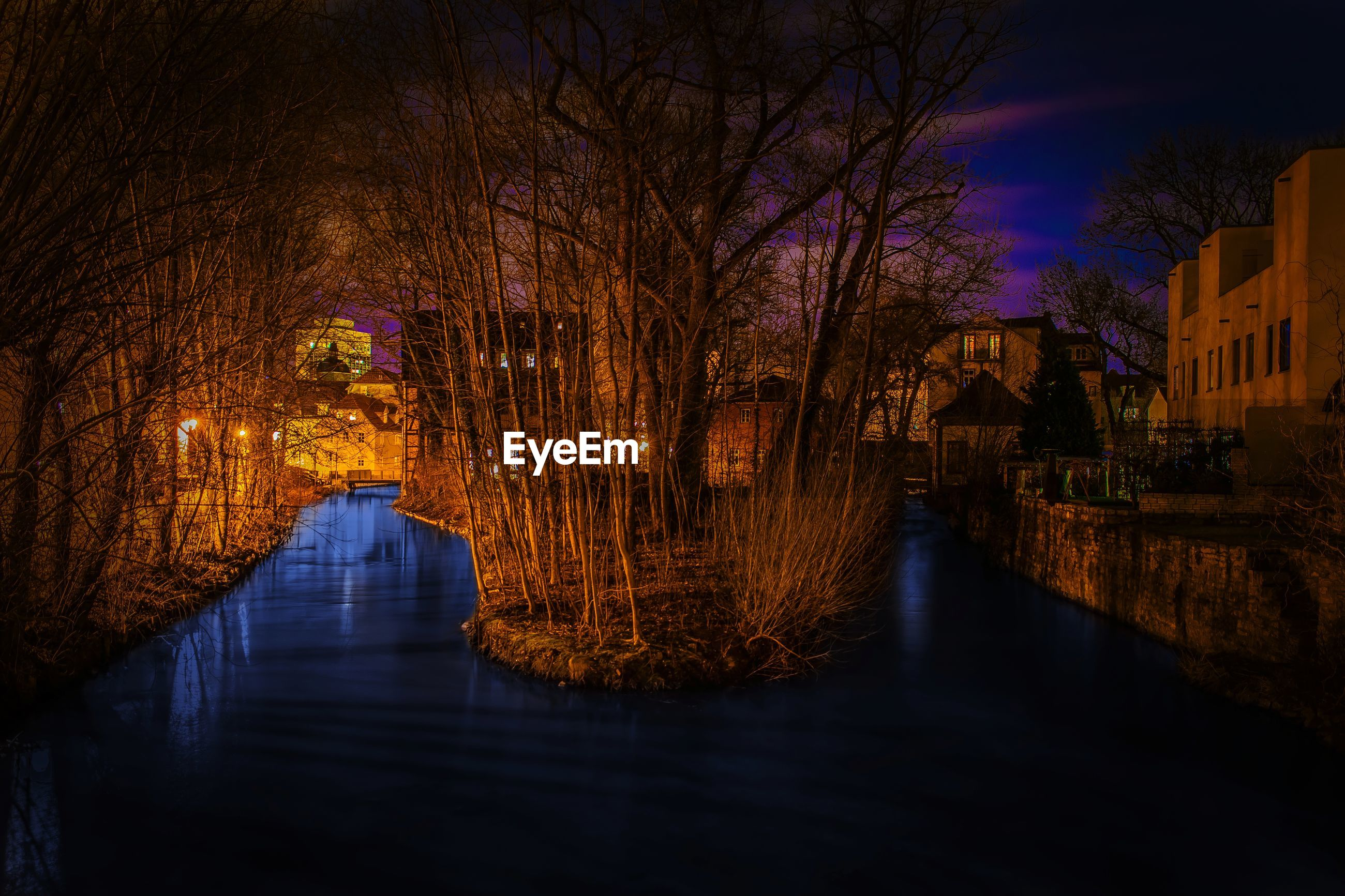 BRIDGE OVER CANAL AMIDST BUILDINGS AT NIGHT