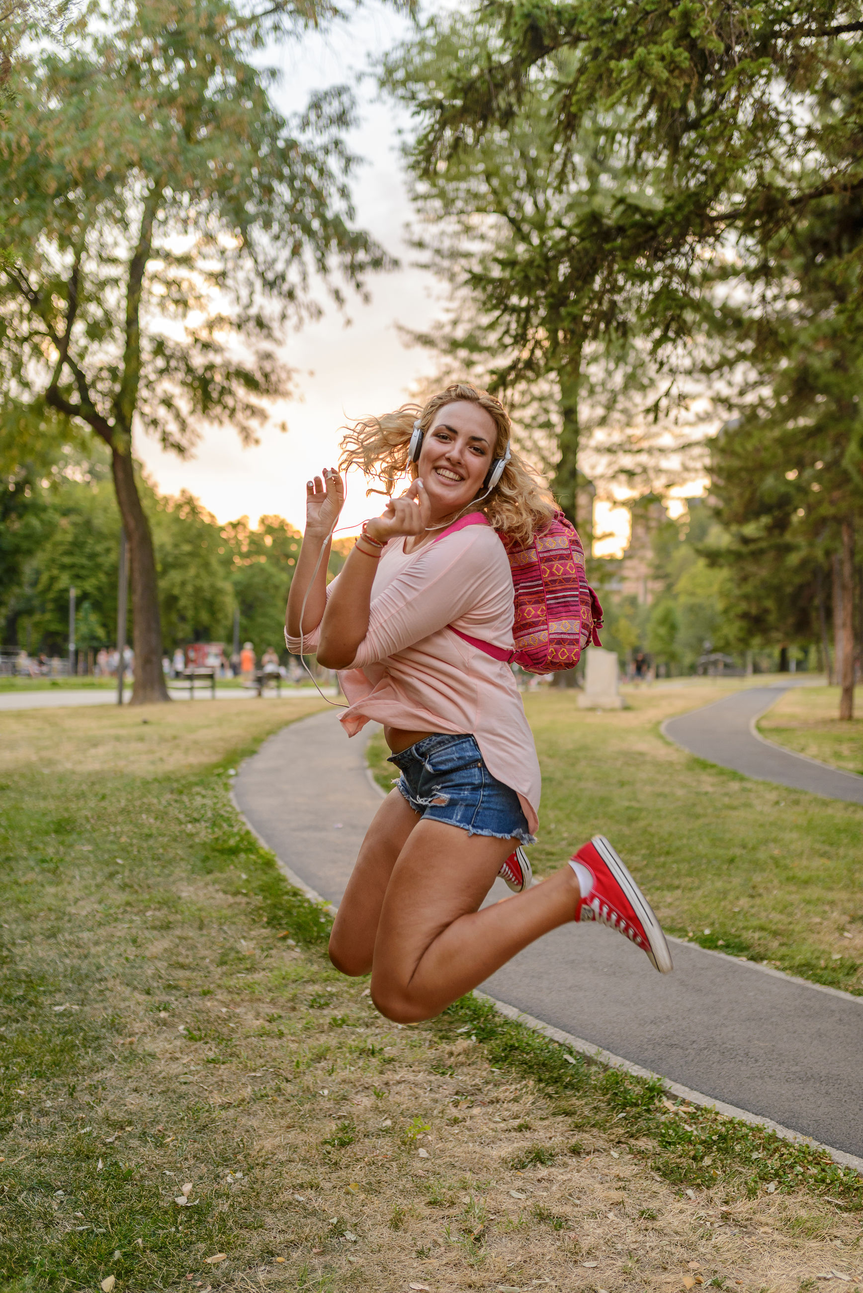 Portrait of smiling young woman listening music while jumping in park