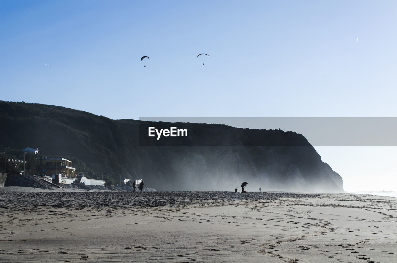 Scenic view of cliff at beach against clear sky